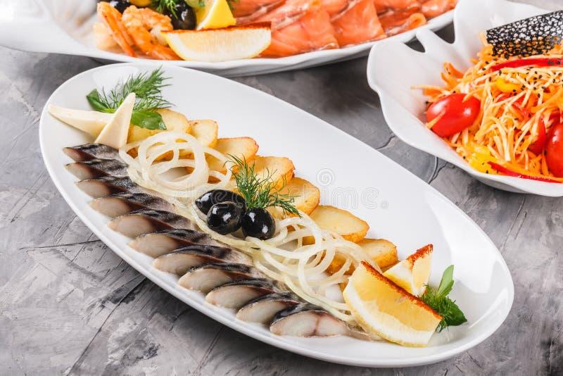 Havs- uppläggningsfat med skivan för rökt makrill, stekte potatisar, skivafiskfilé som dekoreras med löken över lantlig bakgrund royaltyfri fotografi