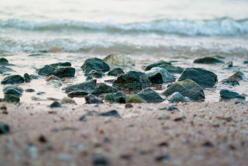 Havsbränning på stranden med stenen arkivfoto