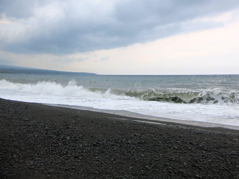 Havsbr?nning och v?gor som kraschar mot en svart sandstrand i Bali royaltyfria foton