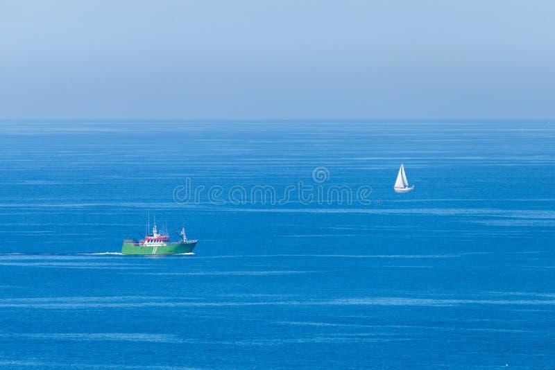 Havsfisherskepp och segelbåt i ett hav Minimalist sikt royaltyfri fotografi