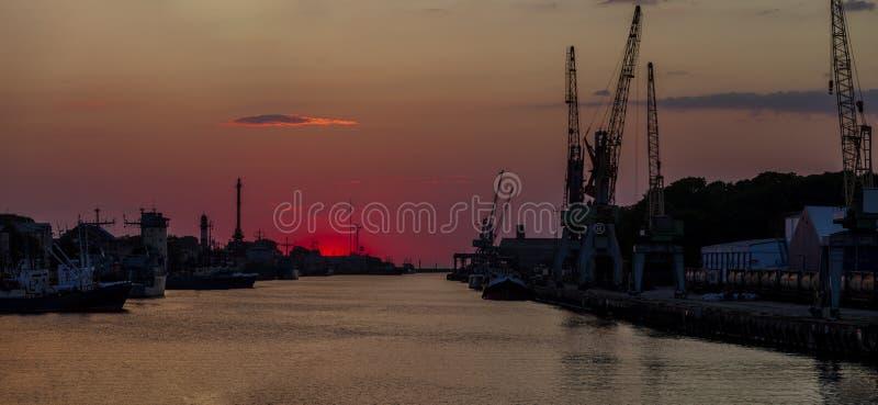 Havshamnsiuette i solnedgången, Liepaja, Lettland royaltyfria foton