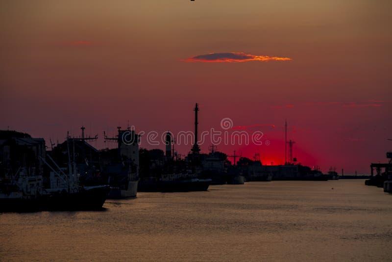 Havshamnsiuette i solnedgången, Liepaja, Lettland royaltyfri fotografi