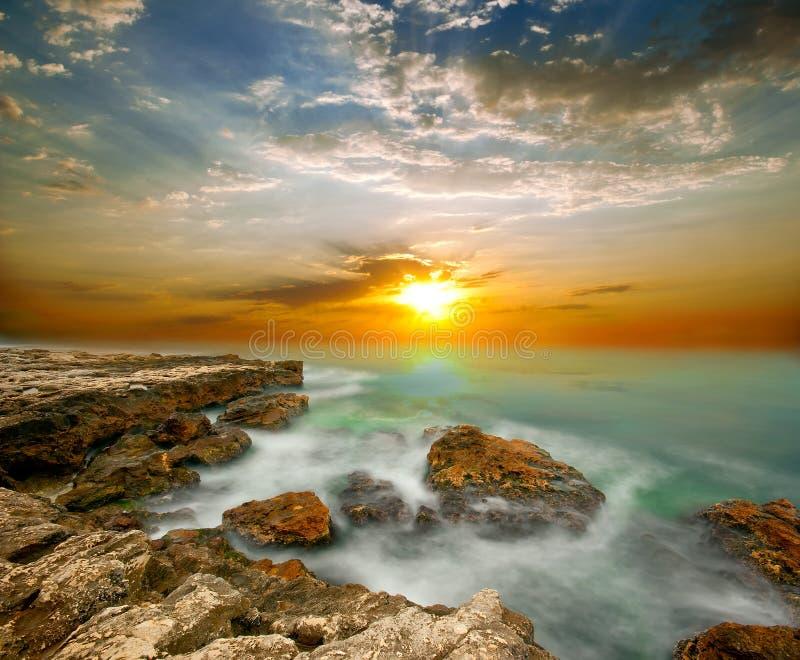 Havsklippor och solnedgång över havet royaltyfri bild