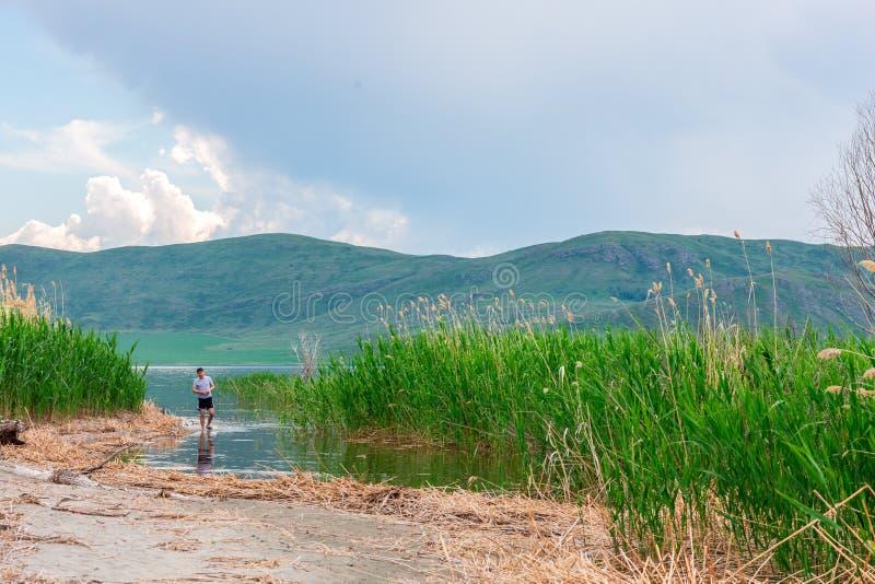 Havslandskap med mountines och rottingar, blå himmel med moln, cloudly utan solen, kazakhstan arkivfoto