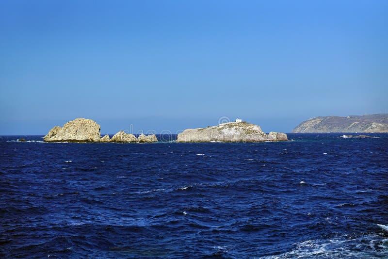 havslandskap och klippor med en liten enslig kyrka nära ön av Paros arkivbild
