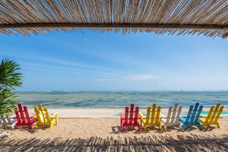 Havslandskapställe som mediterar på stranden med färgrika stolar royaltyfria bilder