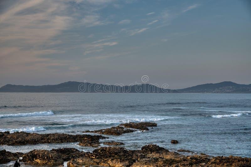 Havsolnedgånglandskapet med vågor fördunklar och vaggar Natur sand royaltyfri fotografi