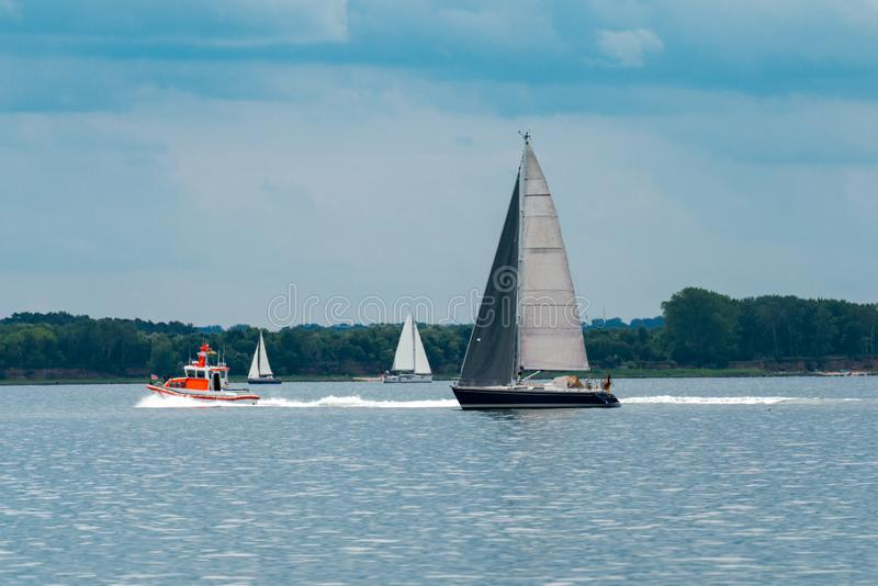 Havspanorama med tre segelbåtar och en livräddningsbåt royaltyfri bild