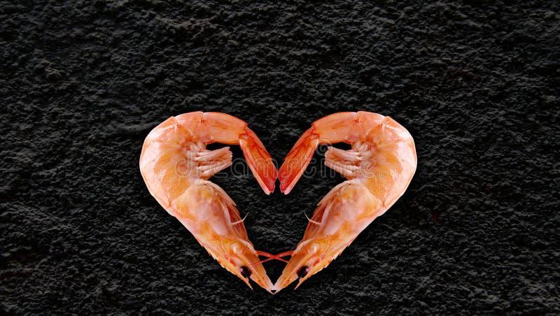 Havsprodukter, hjärta formade räka, svart bakgrund baktill för att skriva din artikel royaltyfri bild