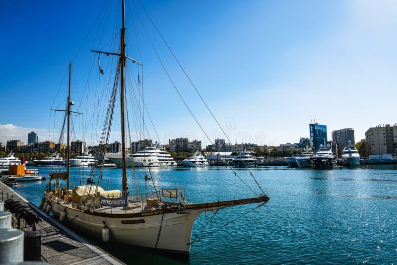 Havssikt med yachter i Barcelona port Solstrålar på havsvågor Cityscape hus Härligt utomhus- landskap med skepp royaltyfria foton