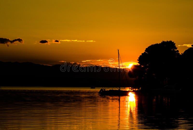 Havssolnedgång i segelbåt arkivfoto