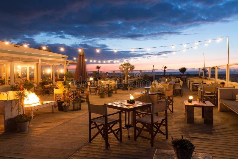 Havssolnedgång med folk i en restaurang längs den holländska kusten av Scheveningen arkivfoton