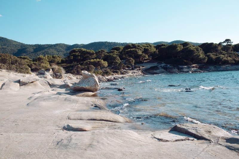 Havsstrand med bergigt landskap på solig blå himmel Stenig strand med blått vatten och gröna träd Sommarsemester i vändkretsen arkivfoton