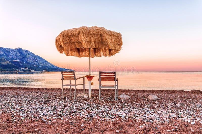 Havsstrand på soluppgång, strandparaplyet och chaisevardagsrum arkivfoton