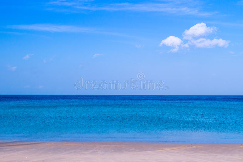 Havsstranden med blå himmel och gul sand och några fördunklar ovanför la arkivfoto