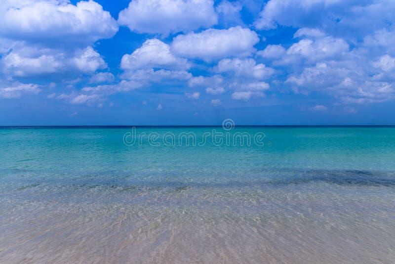 Havsstranden med blå himmel och gul sand och några fördunklar ovanför la arkivbilder