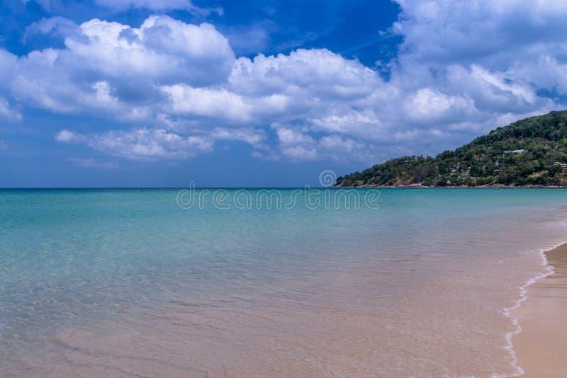 Havsstranden med blå himmel och gul sand och några fördunklar ovanför la arkivbild
