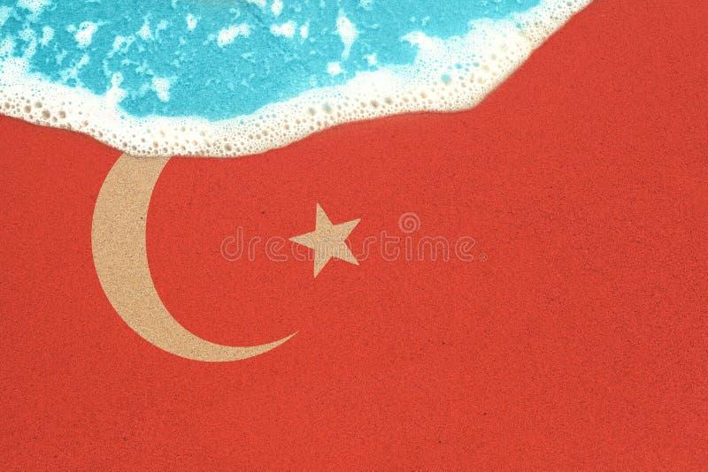 Havsvåg på den soliga sandiga stranden med flaggan Turkiet r royaltyfri bild