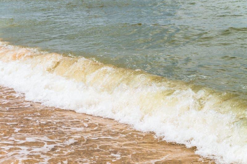 Havsvågen kör kraftfullt på den sandiga kusten royaltyfri foto