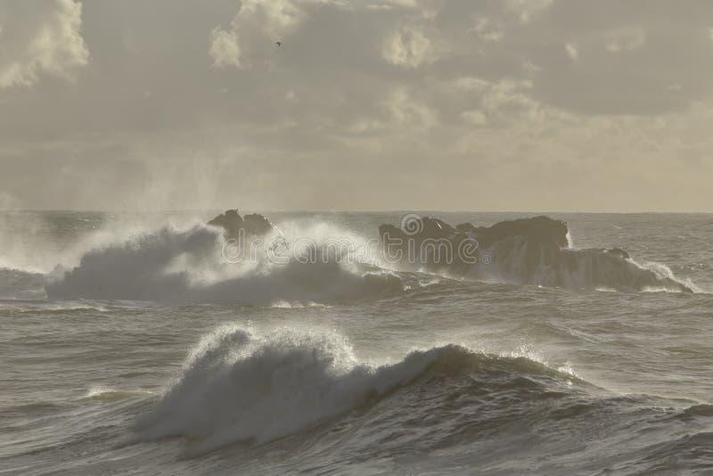 Havsvågor över vaggar på solnedgången royaltyfria bilder