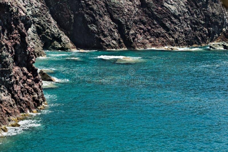 Havsvågor bryter på vaggar av det Ligurian berget Nära Cinque Terre en seascape med det blåa havet och mörkt - rött vaggar by arkivbild