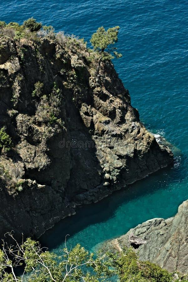 Havsvågor bryter på vaggar av det Ligurian berget Nära Cinque Terre en seascape med det blåa havet och mörkt - rött vaggar arkivfoto