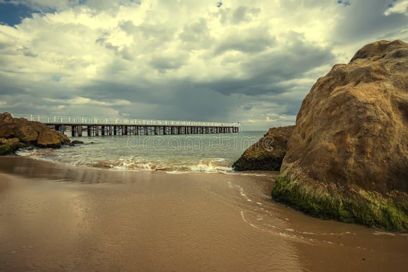 Havsvågor med pir och stora stenar på stranden royaltyfria foton