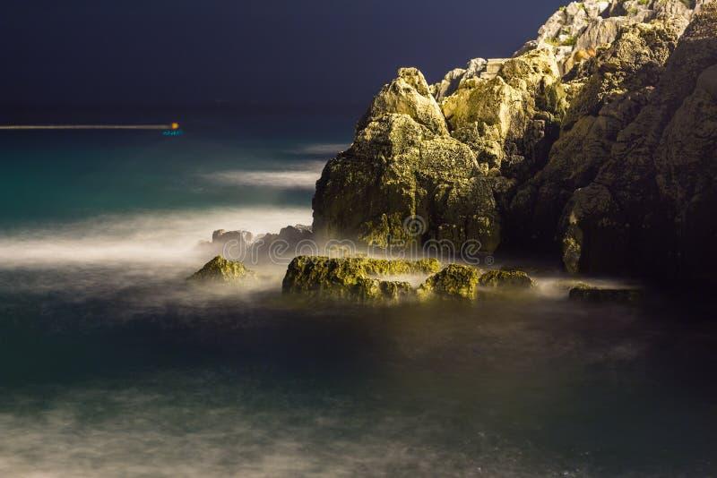 Havsvågor piskar linjen inverkan vaggar på stranden i natt arkivfoton