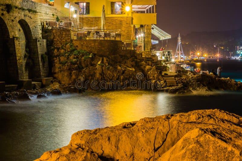 Havsvågor piskar linjen inverkan vaggar på stranden i natt royaltyfria foton