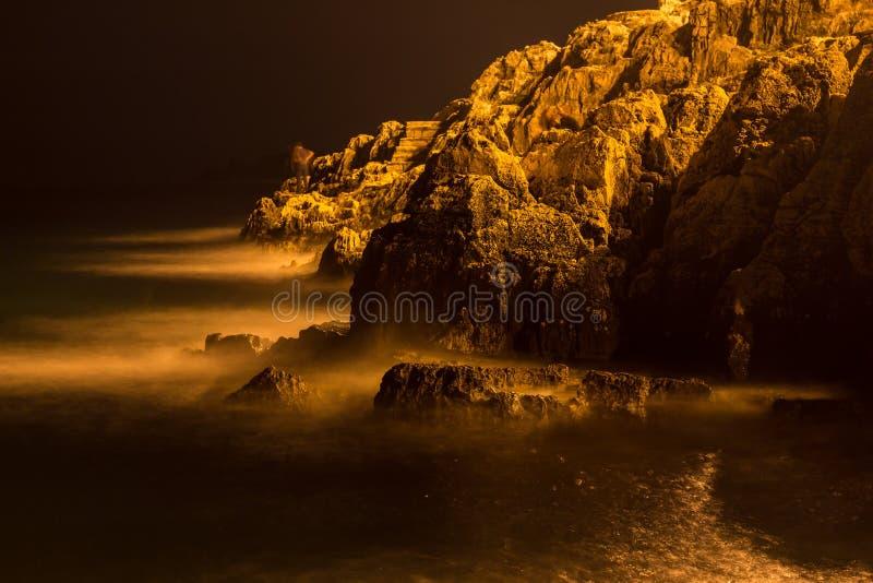 Havsvågor piskar linjen inverkan vaggar på stranden i natt royaltyfri bild