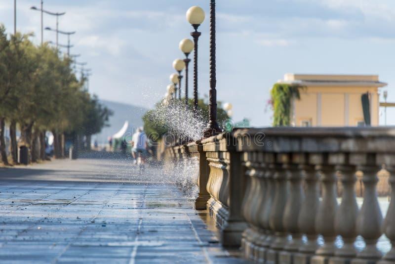 Havsvågor som bryter mot kustpromenad i Windy Day: Stormigt väder royaltyfria bilder