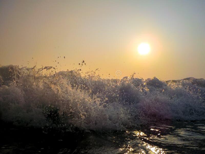 Havsvågor som kraschar mot, vaggar, på solnedgången royaltyfri bild