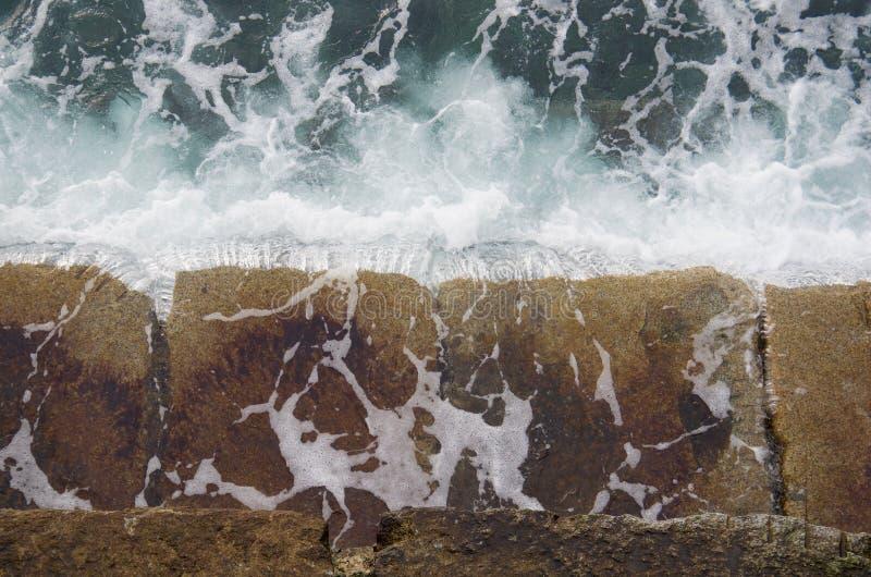 Havsvatten från avbrottsvågor häller från stenar av vågbrytaren arkivfoton