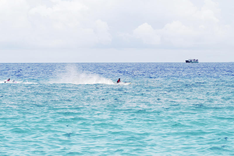 Havsvattenlandskap med lastfartyget på horisont och snabba motorbåten royaltyfria foton