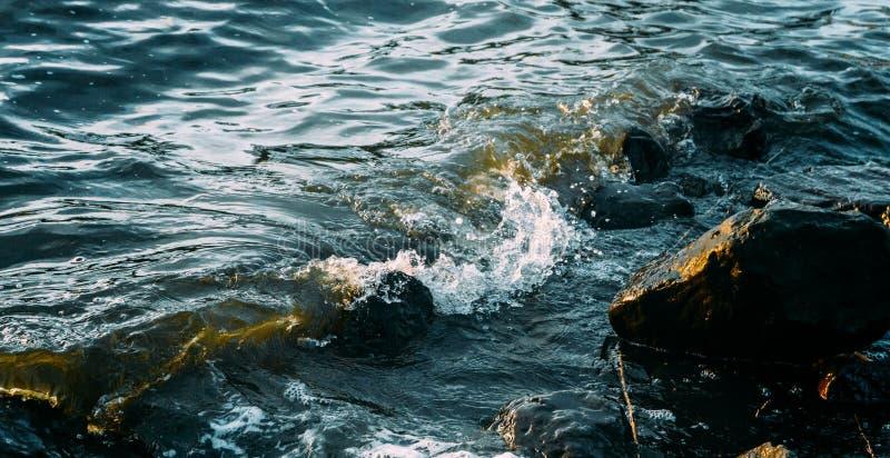 Havsvattenvågor som skjuter på stenarna arkivfoto