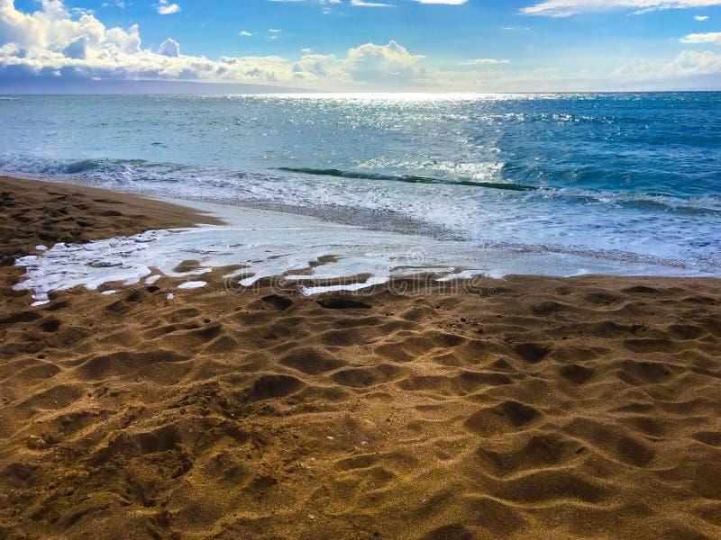 Havtidvatten på Sandy Beach med ljus molnig himmel royaltyfri foto