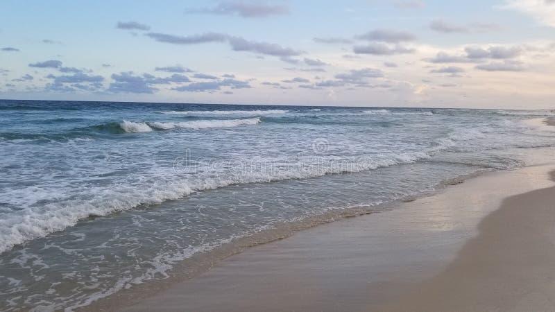 Havvågor på en strand under sommarsolnedgång arkivbild