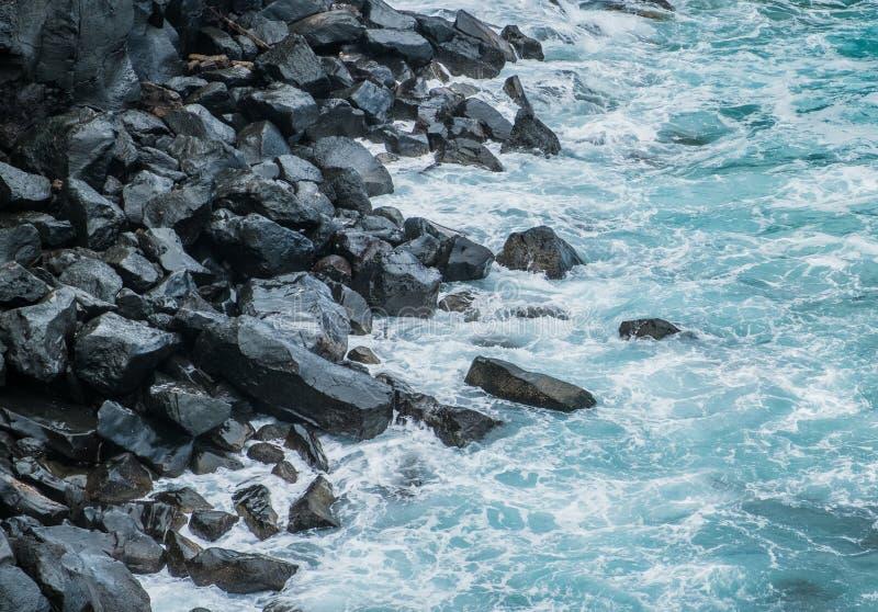 Havvågor på svart kiselstenstenkust royaltyfri fotografi