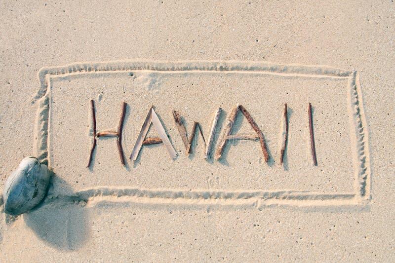 Hawaï dat met stokken op het zand wordt geschreven stock afbeeldingen