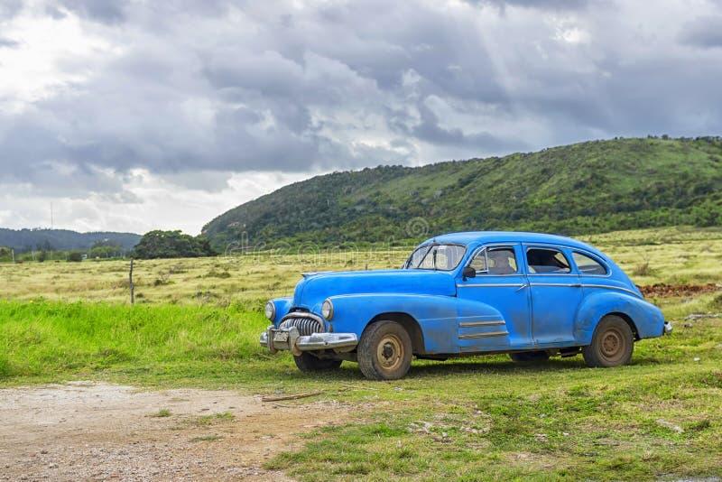 HAWAŃSKI, KUBA, STYCZEŃ - 04, 2018: Retro klasyczny Amerykański samochód parkujący przeciw tłu góry i chmurzący niebo w Kuba fotografia stock