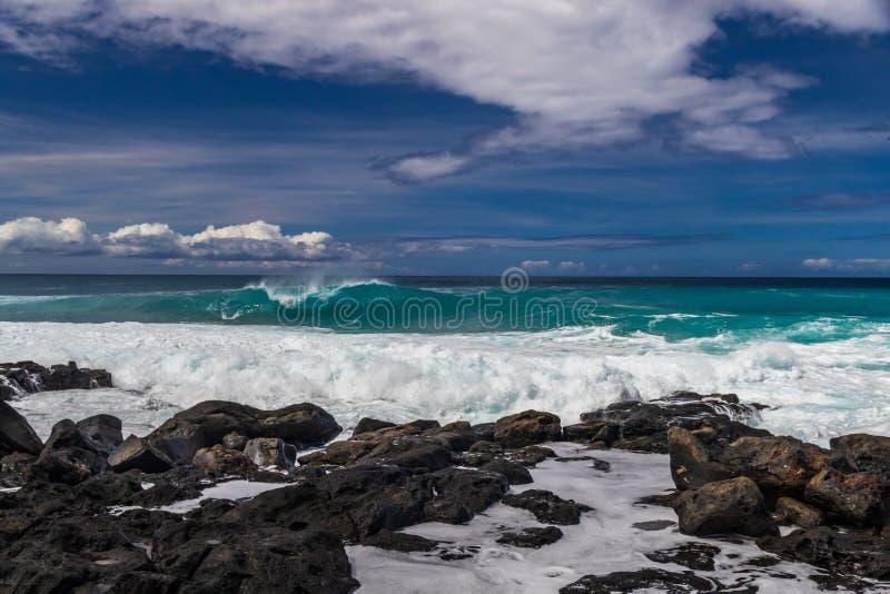 Hawaiansk strand; vulkaniskt vaggar och formen på shoreline; frånlands- vågavbrott Stillahavs- blå himmel och moln i avstånd arkivfoto