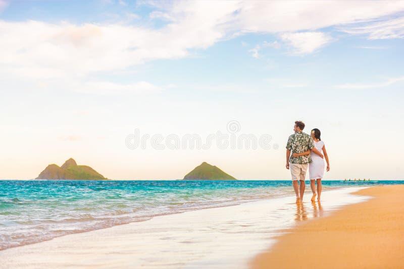 Hawaii beach vacation couple walking at sunset luxury travel holiday honeymoon destination. Newlyweds happy on Lanikai beach, Oahu. Hawaii stock photos