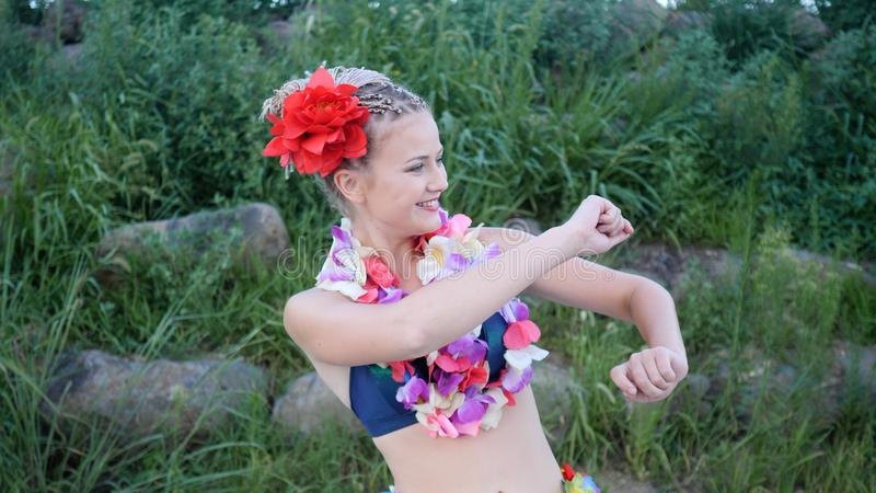 Hawaii girl with braided hair and flowers having fun and silly dancing with flower lei garland stock image