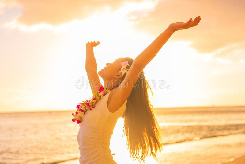 Hawaii hula dancer woman wearing flower necklace lei on sunset beach dancing with open arms free in sunset relaxing on hawaiian stock photography