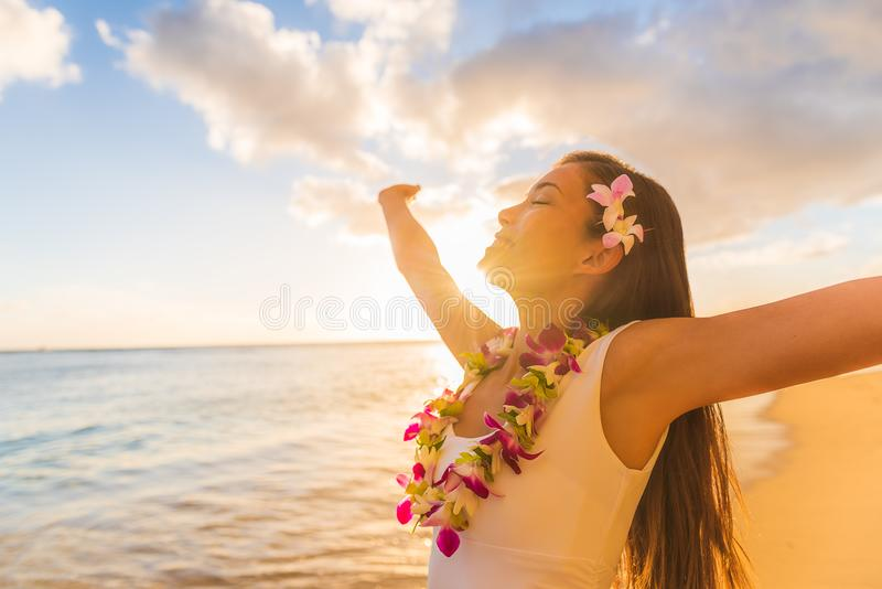 Hawaii hula luau woman wearing hawaiian lei flower necklace on Waikiki beach dancing with open arms free on hawaiian vacation. royalty free stock photo