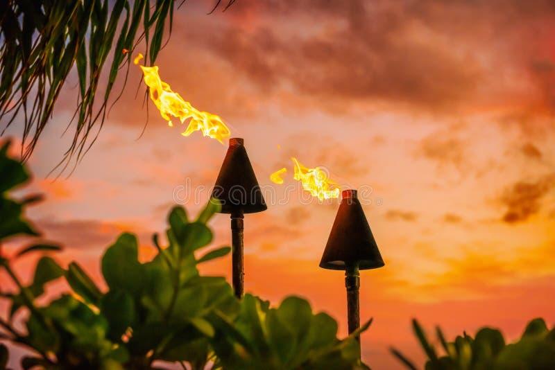 Hawaii luau Party Maui feuFeuertiki Fackeln mit offenen Flammen brennend bei Sonnenuntergang Wolken in der Nacht. Hawaiianische Ku stockfotografie