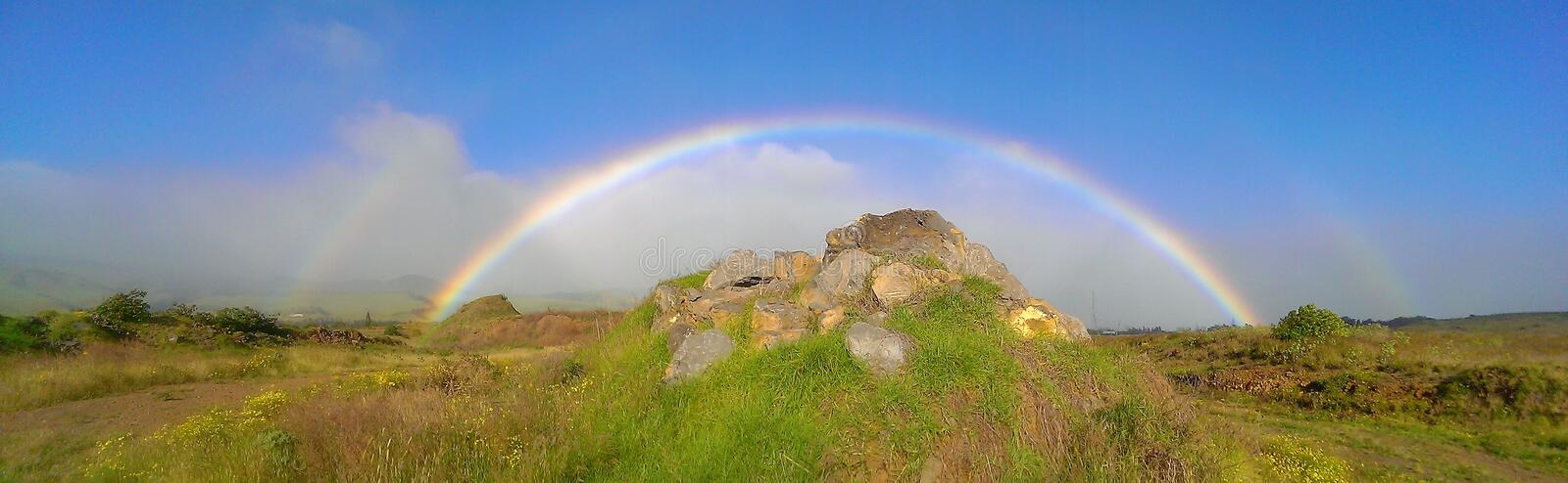 Hawaii rainbow over a rock pile in open field. Rainbow in Waimea Hawaii over a rock pile in an open field royalty free stock image
