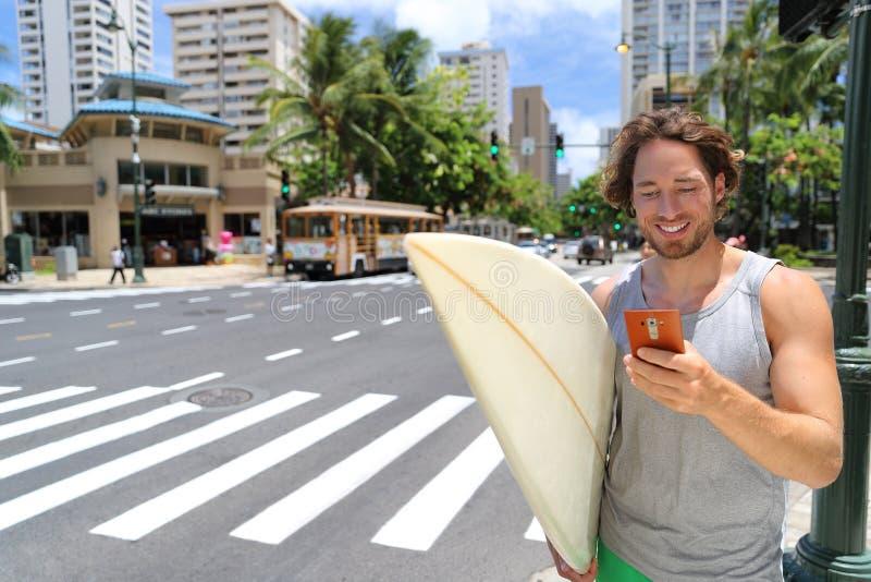 Hawaii surfer man Honolulu livsstil med telefon royaltyfri fotografi