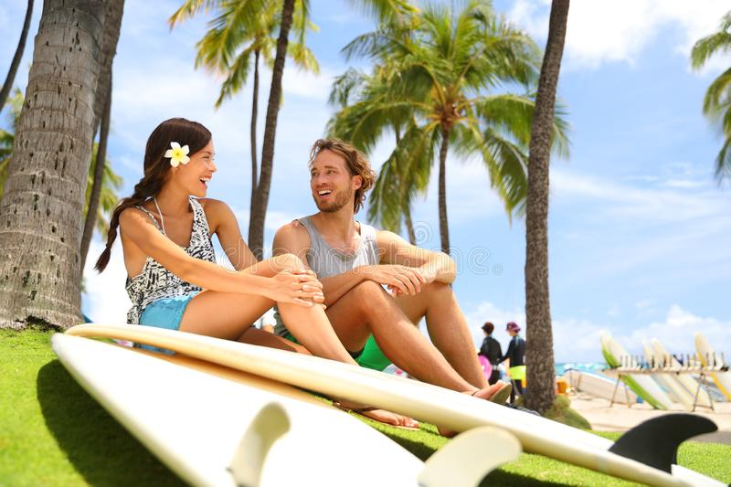 Hawaii surfers people lifestyle happy living couple talking on Waikiki beach relaxing from surfingwith surfboards in Honolulu city. Friends laughing having fun royalty free stock photos