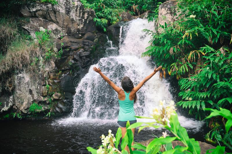 Hawaii travel nature waterfall woman hiker at Canyon Trail Waipoo Falls in Waimea, Kauai island, USA. Freedom happy girl with open. Arms meditating yoga in royalty free stock images